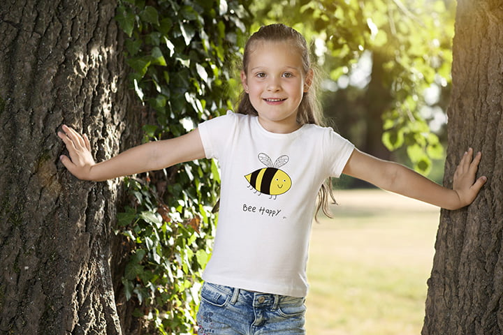 A young girl standing between two trees wearing a white t-shirt with an illustrated smiling bee and the words 'bee happy'